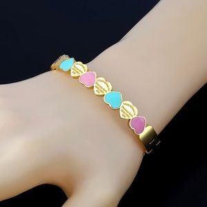 Gold cuff bracelet with blue and pink hearts